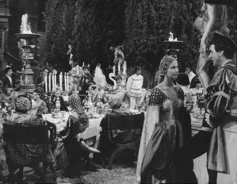 A man and a woman in a movie scene standing and talking at a banquet in Villa Medici.