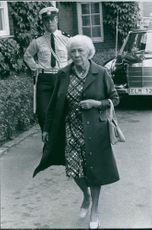 """An old woman walking and a officer looking at her.   """"Rudebeck, Astrid __"""""""
