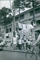 Vietnamese men putting posters on the post and walls on the side of the street of Hanoi during the war in Vietnam.