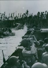 U.S. soldiers scan the skies for Japanese planes as they prepare to swarn ashore from landing barges to establish a beach head at Arawe, New Britain.