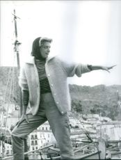 A photo of a Greek actress, singer and politician Melina Mercouri standing on a boat and pointing to something while standing. 1966