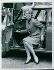 Woman siting in the car and smiling. 1962