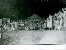 Tribal people photographed together with their weapon.