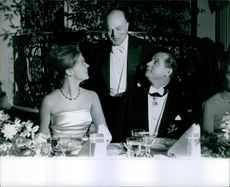 A photo of a man and Princess Birgitta of Sweden sitting together talking to a man standing beside them during party.