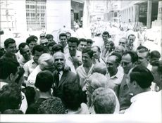 Portrait of a Greek military man Stylianos Pattakos standing and hugging a man, people gathered and smiling.