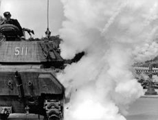 Military tank with with smoke.