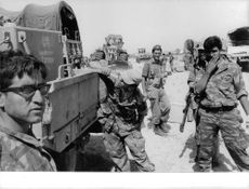 Soldiers looking at the camera while the other soldier is drinking water from the truck. Israel.