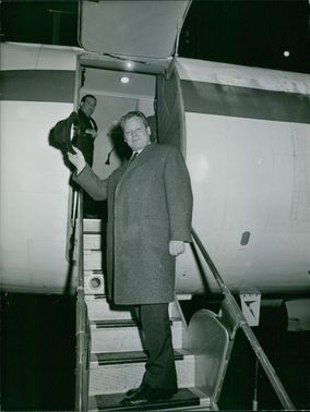 A photo of  a German statesman and politician, who was leader of the Social Democratic Party of Germany (SPD) from 1964 to 1987 and served as Chancellor of the Federal Republic of Germany from 1969 to 1974 Willy Brandt  standing on the stair of airplane.