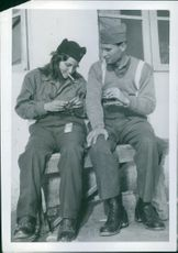 Two Partisans from battle are lighting up their cigarette. 1944