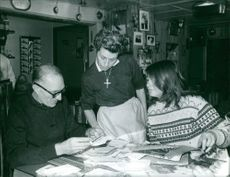 Marielle Goitschel reading documents with a man and woman.