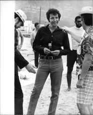 Herb Alpert standing, talking to a man, smiling, on the beach,