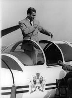 Mohammad Reza Pahlavi getting into the cockpit of an airplane.