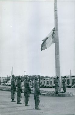 A  flag raise in half mast and soldiers in gun salute.