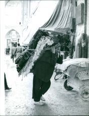 A man walking on the street carrying carpets on his back.