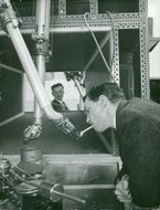 Head of AB Atom Energy's Active Metallurgy section Phil. Dr. Peter Myers gets his cigarette lit by engineer Rune Nånberg