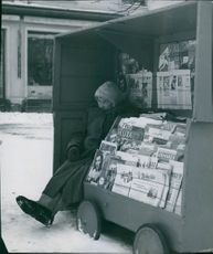 An old woman selling newspaper during winter in Jyväskylä, Finland, 1950.