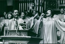"""A scene from the film """"The Preacher's Wife"""", with Whitney Houston as Julia Biggs and Courtney B. Vance as Reverend Henry Biggs, singing, 1996."""
