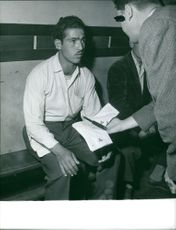 A man holding an evidence knife interrogating another man in Algeria.