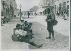 Locals sitting on a pavement.
