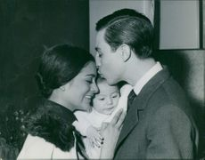 Micaela Flores Amaya, La Chunga receives a kiss from her husband, Jose Luis Gonzalvo while holding their child. 1962.