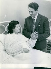 A man holding his wife's hand.