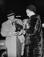 Yul Brynner carrying a small dog.