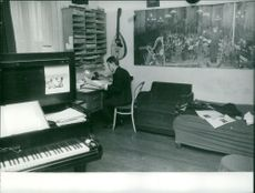 Michel Magne in his room reading notes.