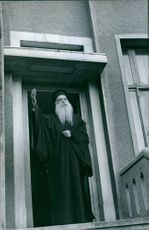 Athenagoras waves his hand by the door.