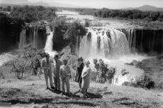 Queen Juliane admiring the giant waterfall with officers and one woman.  5 February 1969