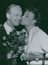 Woman kissing on man's cheek and smiling.