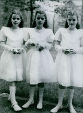 Three little girls are standing together in front of the camera with smiling face. 1964.