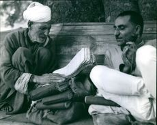 Two men sitting together and communicating with each other.