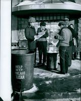 1960 Men standing together and reading newspaper, trash can in the middle.