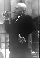 Yul Brynner smoking and taking photograph.