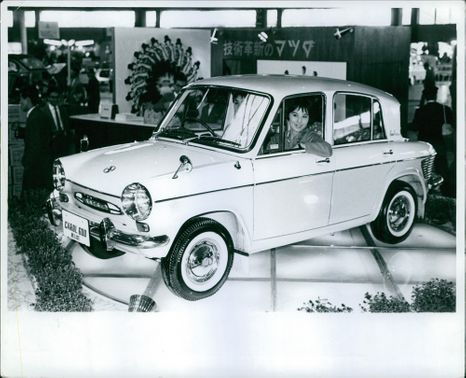 A model of a car and a woman inside smiling.