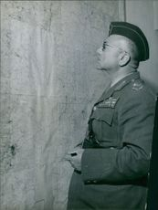 An officer looking at the map stick on the wall.