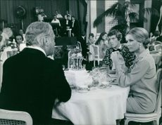 Curd Jürgens, Geneviève Gilles and Michael Crawford at the same table, talking to each other.