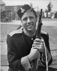 """Photography on actor Peter Lawford wearing full military equipment during the recording of the movie """"Rogue's March""""."""