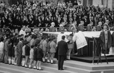 Pope Paul VI standing in among people.