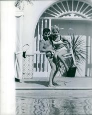 Marty Ingels seen trying to throw a woman into the pool. 1967.