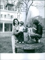 Italian-born actress Marisa Pavan seen with her child Jean-Claude Aumont beside of a sculpture, while a girl name Marie inspecting something on the sculpture