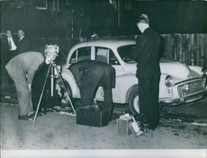People standing and investigating beside the car.