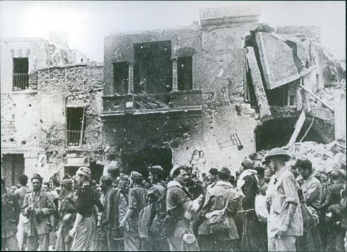 Italian prisoners grouped in front of a wrecked building.