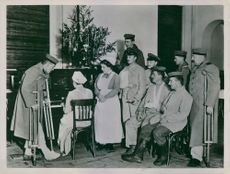 German soldiers enjoying woman playing piano in the healthcare facility during WWI. 1915