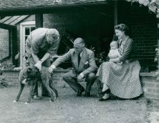 Phyllis Calvert holding her young child while looking at their dog. 1954