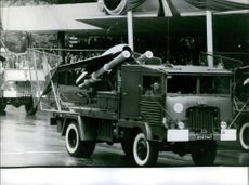 Military vehicles in street during a parade.1962