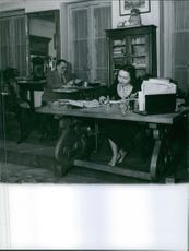 Man and woman siting in the drawing room, working.