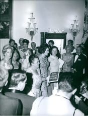 Elsa Maxwell surrounded by people at the 1957 April in Paris Ball.