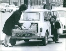 Woman closing the car filled Dicky and talking to man sitting on driving seat.