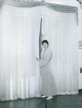 Vintage photo of a woman smiling and holding a floor length curtain.